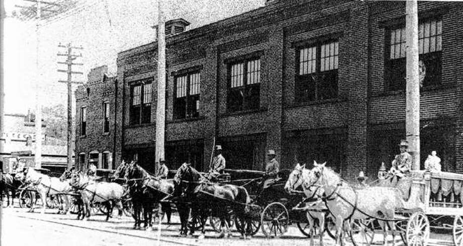 The Chas. Seibold Livery Stable was located at Fourth and Piasa streets. Seibold purchased the first ambulance to be used in the area in 1905. In 1912, he constructed the two-story brick structure in the photograph. It was heated by hot water, and had electricity. Seibold used a special vacuum to clean his horses. The huge Beall Brothers factory can be seen in the background. There were several livery services in Alton, with a variety of carriages and conveyances. The white hearse and horses were used for children's funerals. Photo: File Photo