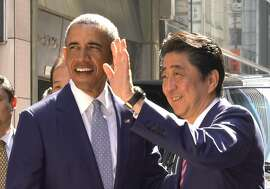 Former U.S. President Barack Obama, left, and Japanese Prime Minister Shinzo Abe pose for photographers,  in front of a Japanese Sushi restaurant in Tokyo's Ginza shopping district, Sunday, March 25, 2018. Obama says negotiations with North Korea on its nuclear weapons program are difficult, partly because the country's isolation minimizes possible leverage, such as trade and travel sanctions against Pyongyang. (AP Photo/Shizuo Kambayashi, Pool)