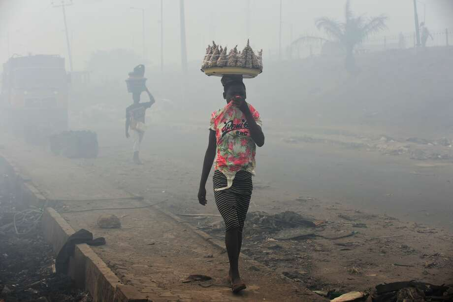 Vendors cover their nose to walk in the smokes from Olusosun dump site at Ojota in Lagos, Nigeria's commercial capital on March 22, 2018. Lagos State Government shut down the Olusosun dump site following a fire outbreak from trapped gasses in the waste escaping to cause combustion. The fire left ten vehicles and goods stored in warehouses burnt. The smokes from the dump sites has forced many businesses to close shop and residents to evacuate the neighbourhood following the attendant health hazards from the polluted environment. Photo: PIUS UTOMI EKPEI/AFP/Getty Images