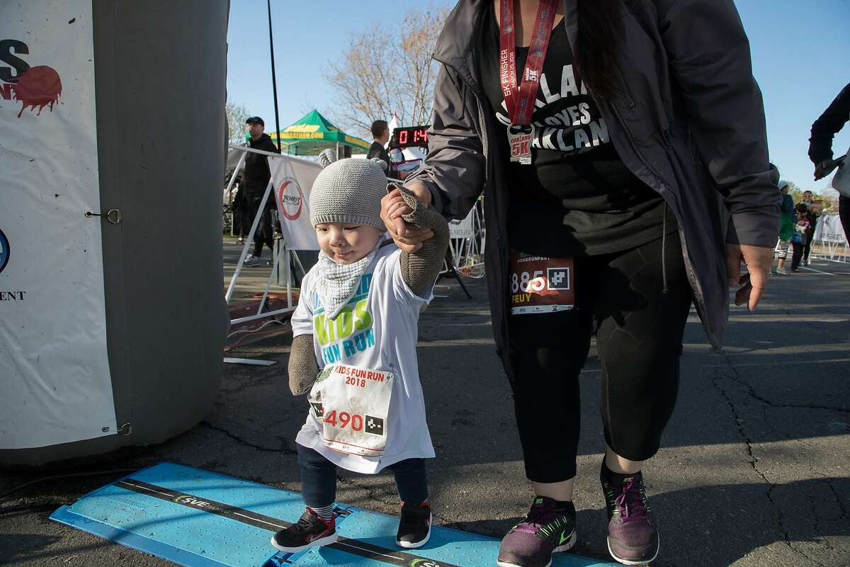 Ian Mar, 16-months, crwith the assistance of mother Feuy, crosses the finish line in the Kids Fun Run on Sunday, March 25, 2018 in Oakland, Calif.