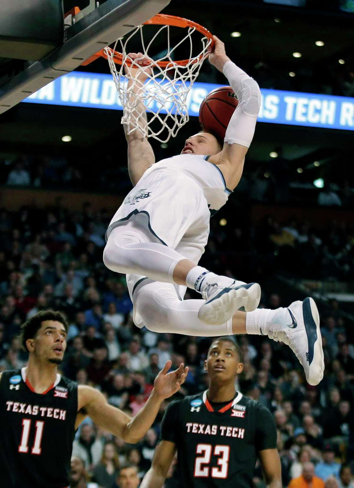 Villanova's Donte DiVincenzo hangs on the rim after dunking over Texas Tech's Zach Smith, left, and Texas Tech's Jarrett Culver, right, during the second half of an NCAA men's college basketball tournament regional final, Sunday, March 25, 2018, in Boston.