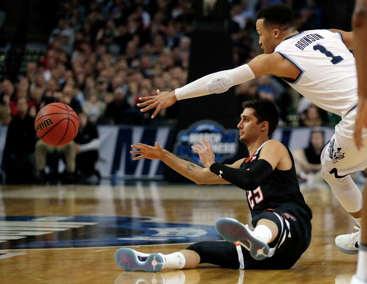 Texas Tech's Davide Moretti, seated, passes the ball as Villanova's Jalen Brunson defends during the second half of an NCAA men's college basketball tournament regional final, Sunday, March 25, 2018, in Boston.