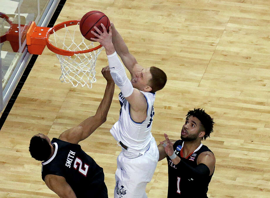 Villanova's Donte DiVincenzo, center, dunks between Texas Tech's Zhaire Smith, left, and Brandone Francis during the second half of an NCAA men's college basketball tournament regional final, Sunday, March 25, 2018, in Boston. Photo: Mary Schwalm, AP / FR158029 AP