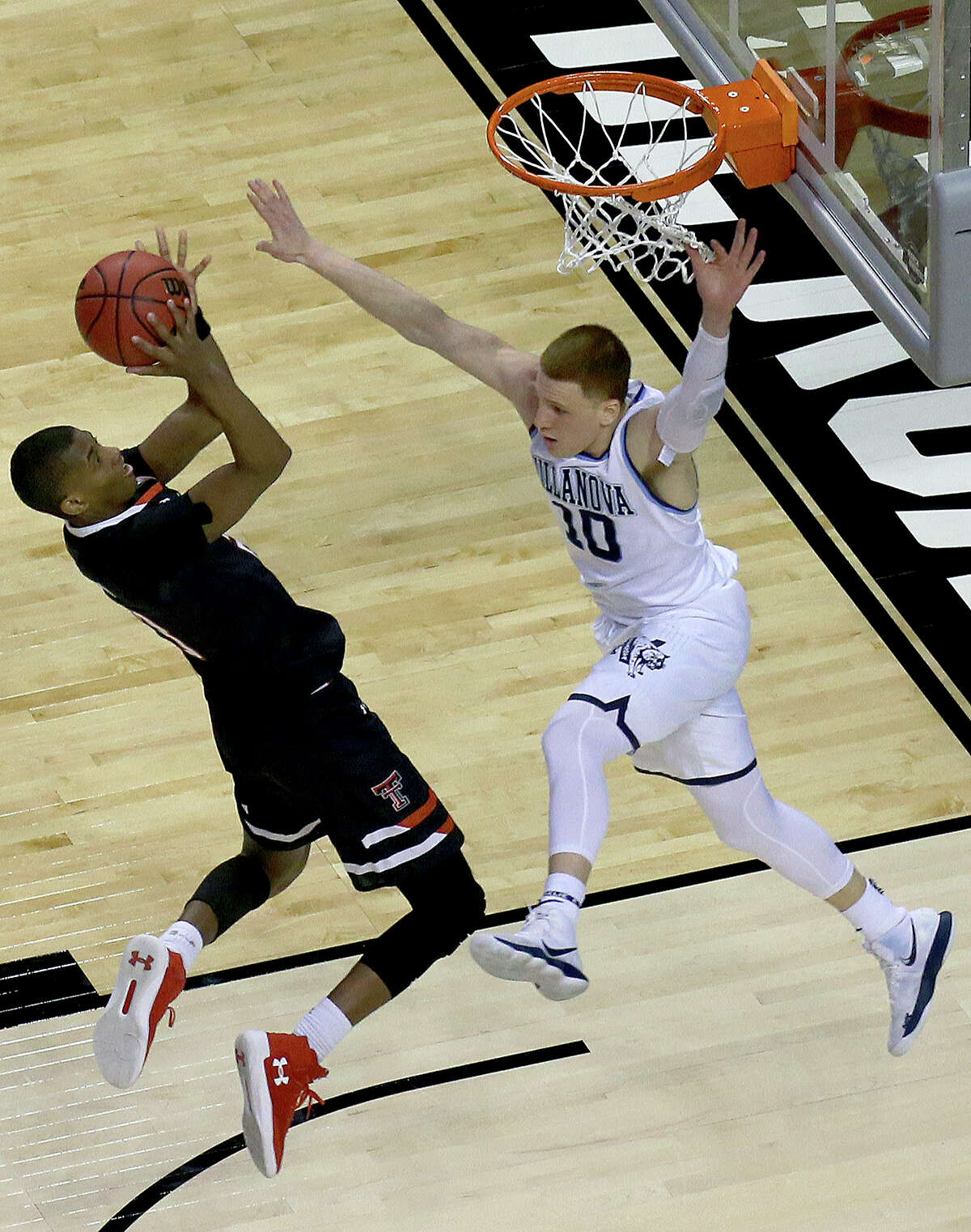 Texas Tech's Jarrett Culver, left, shoots against Villanova's Donte DiVincenzo,right, during the second half of an NCAA men's college basketball tournament regional final, Sunday, March 25, 2018, in Boston.