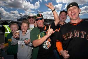 Members of the Kehr, Silva and Hull families, San Francisco Giants and Oakland Athletics fans who live in communites all around the Bay Area, tailgate before a the first game of the Bay Bridge Series,  Sunday, March 25, 2018 in Oakland, Calif.