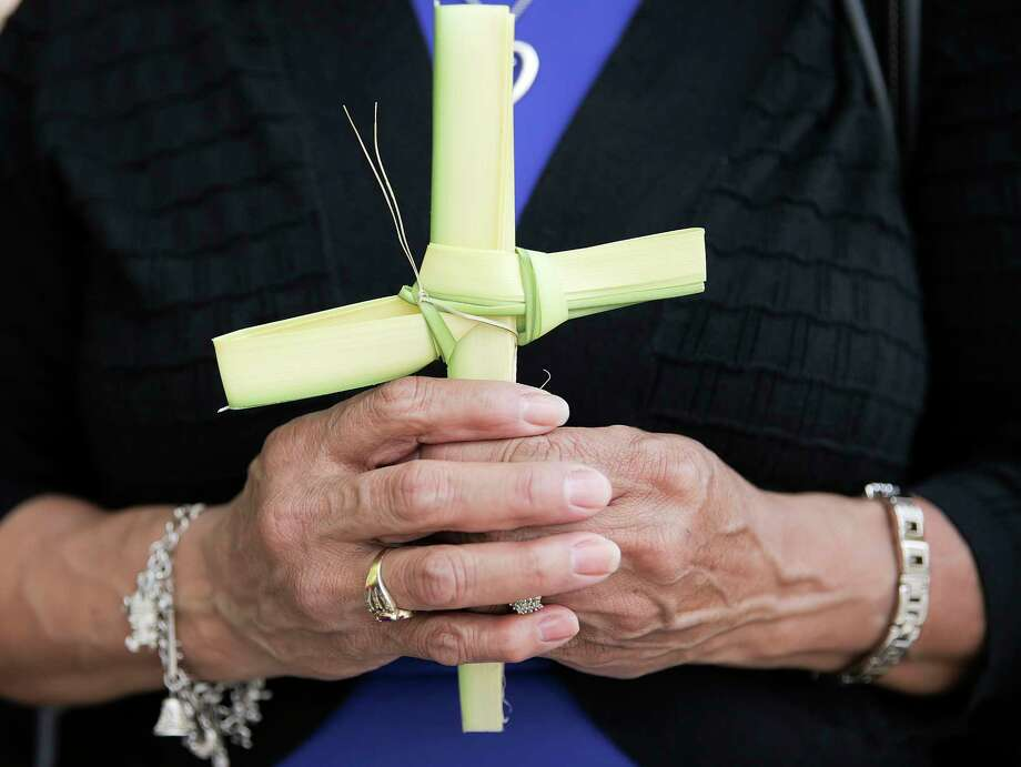 A woman holds onto a palm woven into a cross before Palm Sunday service at Assumption Catholic Church on Sunday, March 25, 2018, in Houston. Photo: Elizabeth Conley, Houston Chronicle / © 2018 Houston Chronicle
