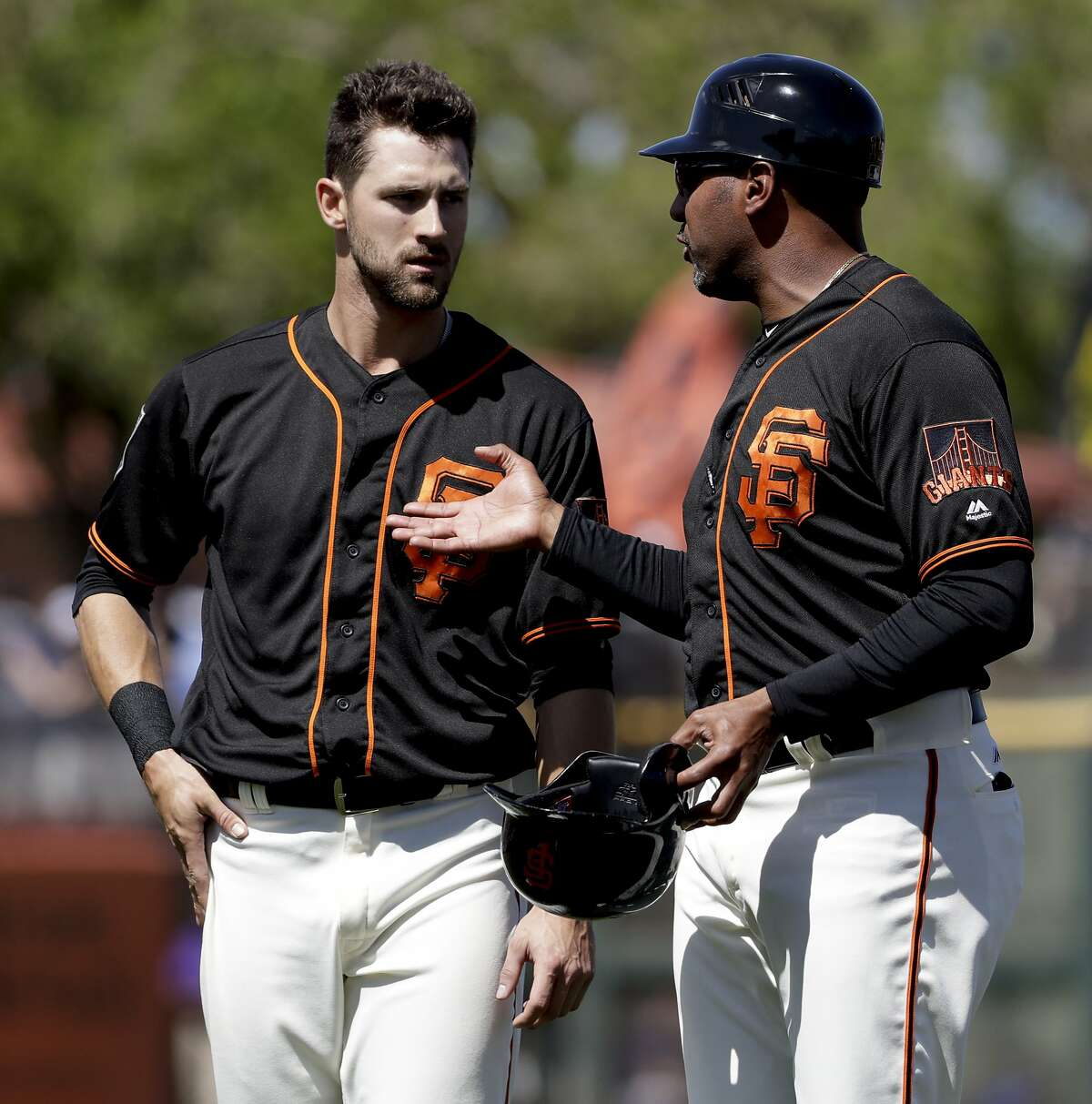 San Francisco Giants first base coach Jose Alguacil, right, talks to Steven Duggar during the first inning of the team's spring training baseball game against the Kansas City Royals in Scottsdale, Ariz., Friday, March 23, 2018. (AP Photo/Chris Carlson)