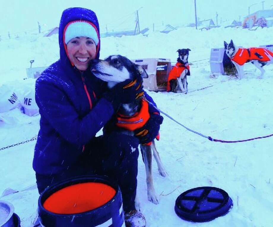 Shaynee Traska with Paxson, one of her two lead dogs, at the end of the 998-mile Iditarod race across Alaska, from Anchorage to Nome. With injury taking the other lead dog out of the race, Paxson led the team for the final 77 miles of the race, which included the 'blow hole' where the wind blows rapidly from all directions and commonly knocks mushers and their dogs off the trail. (photo provided to Daily News)