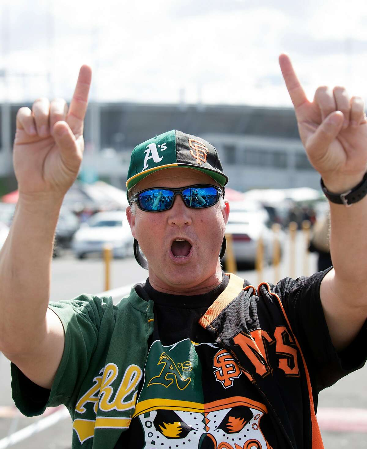 Jeff Kehr of San Ramon, Calif., whose loyalties are obvious split between the Oakland Athletics and San Francisco Giants, tailgates before a the first game of the Bay Bridge Series, Sunday, March 25, 2018 in Oakland, Calif.