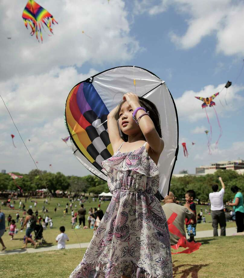 Zoey Lee, 8, checks out kites as she helps her dad with his during the Annual Kite Festival at Hermann Park on  Sunday, March 25, 2018, in Houston. Photo: Elizabeth Conley, Houston Chronicle / © 2018 Houston Chronicle