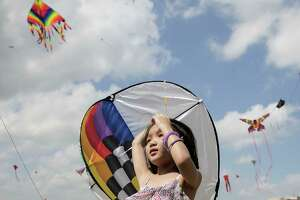 Zoey Lee, 8, checks out kites as she helps her dad with his during the Annual Kite Festival at Hermann Park on  Sunday, March 25, 2018, in Houston.