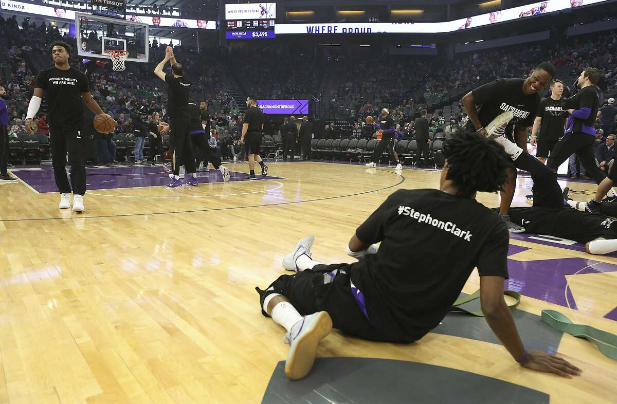 Sacramento Kings guard De'Aaron Fox, right, along with teammates and Boston Celtics players wore a T-shirt in memory of Stephon Clark who was killed in a confrontation with Sacramento Police on March 18 before the start of an NBA basketball game in Sacramento, Calif., Sunday, March 25, 2018. (AP Photo/Steve Yeater)