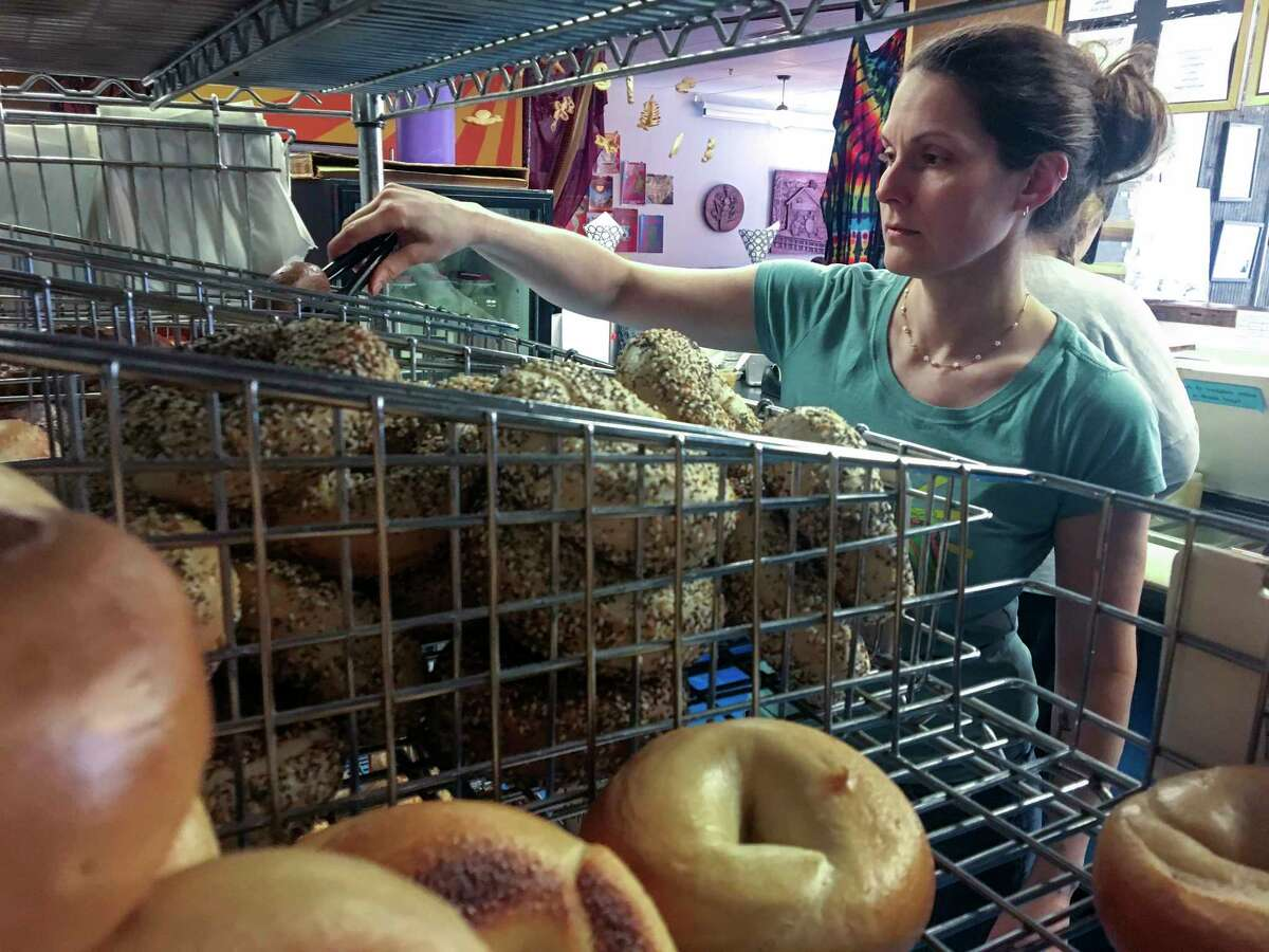 In this Friday, March 23, 2018, photo, Laura Kerrone, owner of the Psychedelicatessen bagel bistro, reaches for a bagel at her store in Troy, N.Y. Kerrone said she looks forward to providing a payroll deduction retirement savings plan to her employees if a state-facilitated program is approved by the Legislature. (AP Photo/Mary Esch)