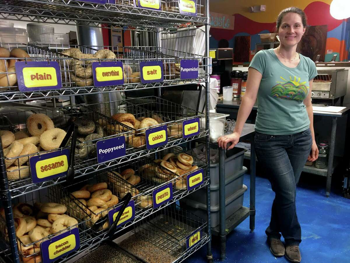 In this Friday, March 23, 2018, photo, Laura Kerrone, owner of the Psychedelicatessen bagel bistro, poses beside a bagel rack at her store in Troy, N.Y. Kerrone said she looks forward to providing a payroll deduction retirement savings plan to her employees if a state-facilitated program is approved by the Legislature. (AP Photo/Mary Esch)