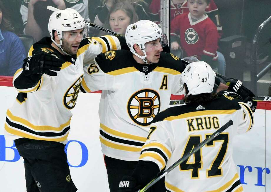 Boston Bruins' Patrice Bergeron (37), Brad Marchand (63) and Torey Krug (47) celebrate a goal by Marchand against the Minnesota Wild during the overtime period of an NHL hockey game Sunday, March 25, 2018, in St. Paul, Minn. The Bruins won 2-1 in overtime. (AP Photo/Hannah Foslien) Photo: Hannah Foslien / FR159563 AP