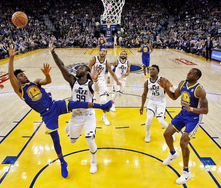 Quinn Cook (4) puts up an off balance shot under the basket in the first half as the Golden State Warriors played the Utah Jazz at Oracle Arena in Oakland, Calif., on Sunday, March 25, 2018.