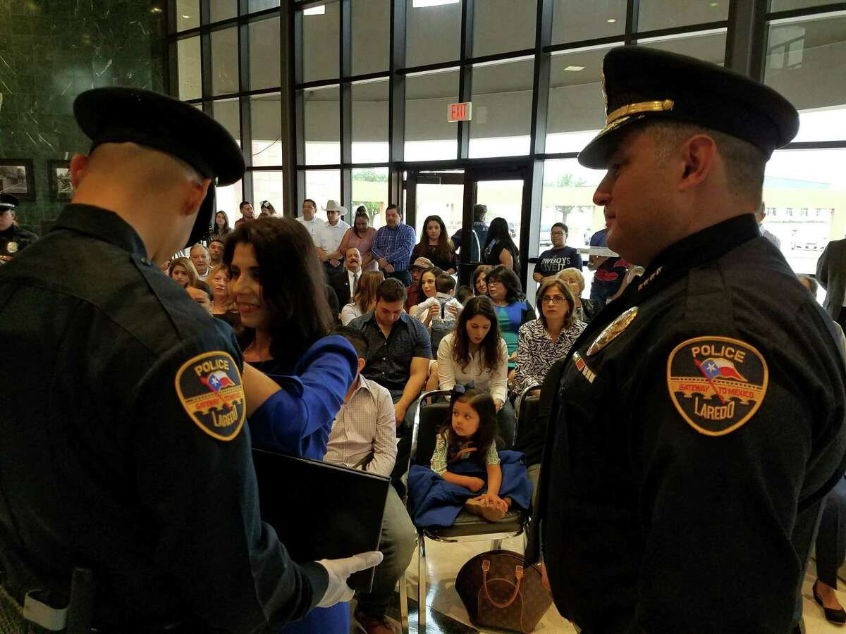 A new police officer receives the badge that accredits him as an agent of the Laredo Police Department during a badge placement ceremony for 12 new officers on Friday morning.