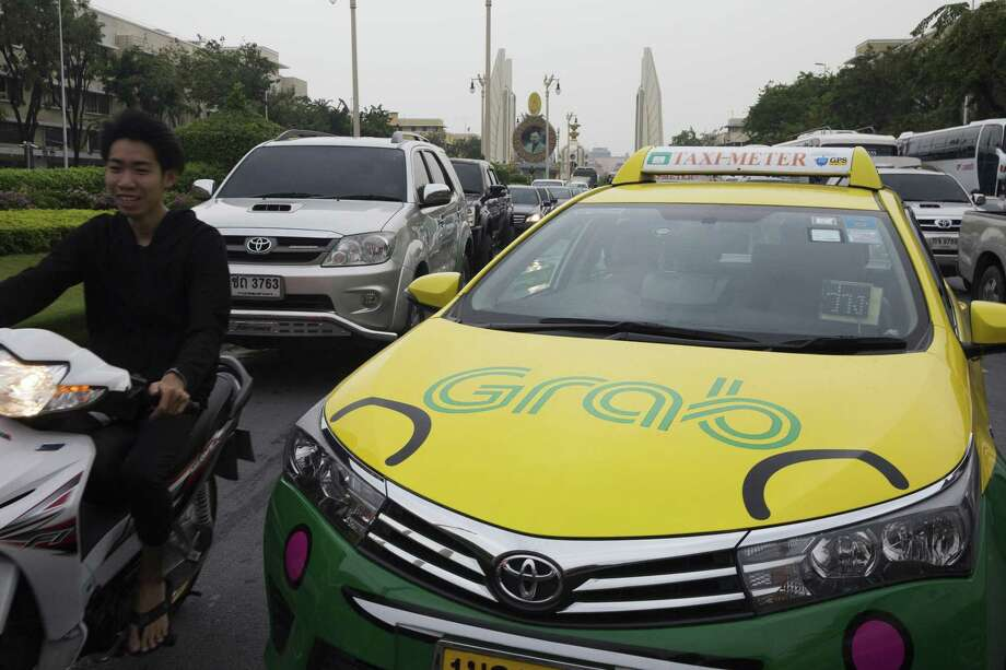 The Grab logo is displayed on a taxi near Democracy Monument in Bangkok, Thailand, on March 9, 2018. Photo: Brent Lewin/Bloomberg / Bloomberg