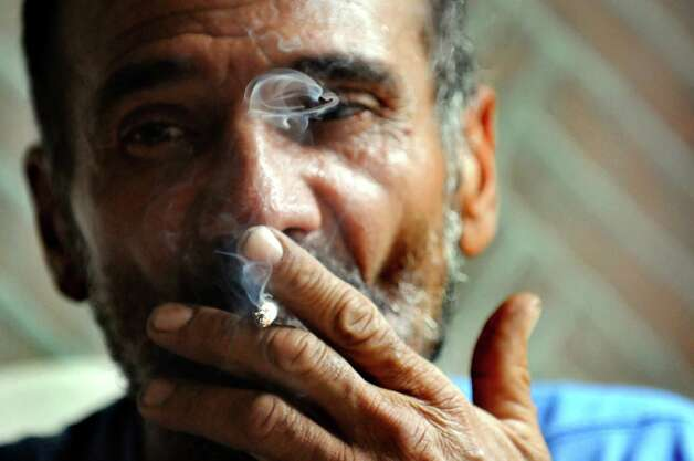 "Samuel ""Poppy"" Baez smokes a hand-rolled cigarette on July 24, 2009, at his apartment on Delaware Street in Albany, N.Y. (Cindy Schultz / Times Union) Photo: CINDY SCHULTZ"