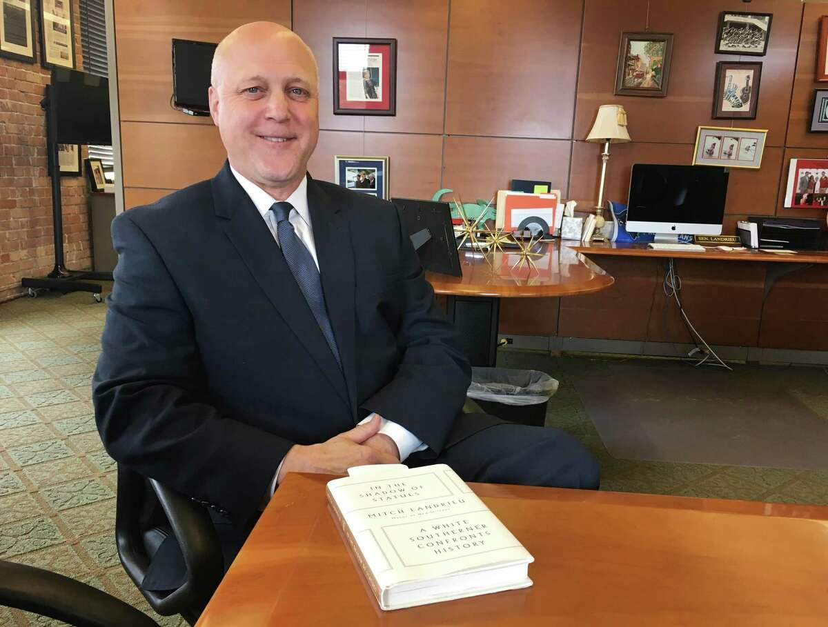 """New Orleans Mayor Mitch Landrieu poses with a copy of his new book, """"In the Shadow of Statues in New Orleans."""" The book is a memoir in which Landrieu discusses the issues of race that affected his personal and political life, and his role in the removal of four Confederate-related monuments from the city landscape."""