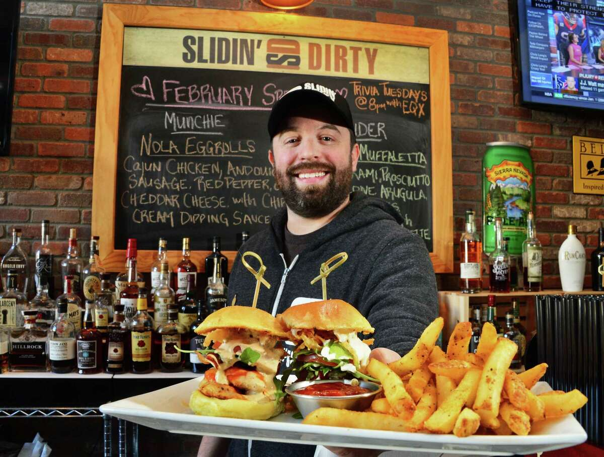 Kitchen manager Brad PichŽ offers up an order of sliders and fries at Slidin' Dirty Wednesday Feb. 14, 2018 in Schenectady, NY. (John Carl D'Annibale/Times Union)
