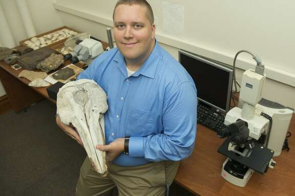 William Gearty, lead author for the aquatic mammal study, holds one of the skulls he examined.