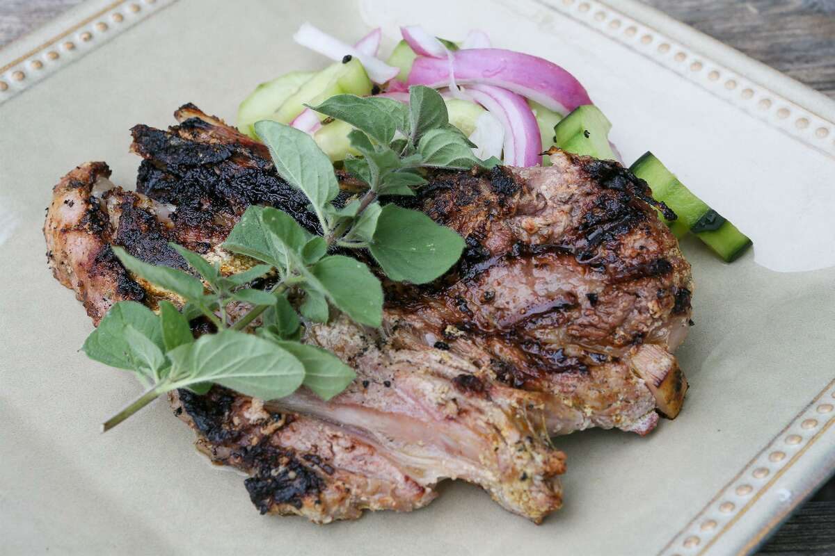 A Greek lamb chop with a sprig of oregano and side of cucumber salad.