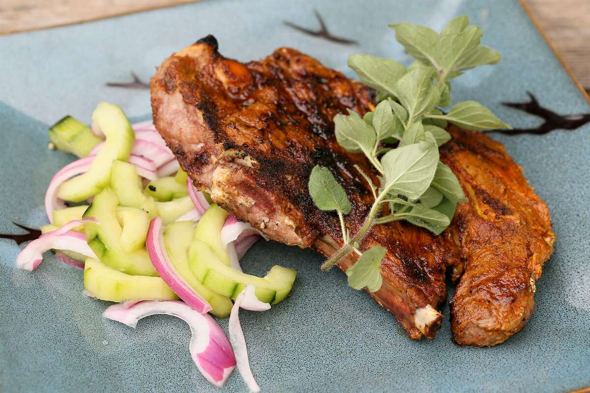 An Indian spiced lamb chop with a sprig of oregano and side of cucumber salad.