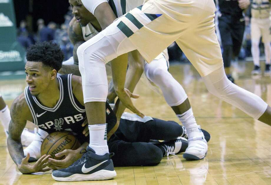 San Antonio Spurs guard Dejounte Murray, left, tries to get a time out called as he battles for the loose ball against the Milwaukee Bucks during the second half of an NBA basketball game Sunday, March 25, 2018, in Milwaukee. (AP Photo/Darren Hauck) Photo: Darren Hauck, FRE / Associated Press / darren hauck
