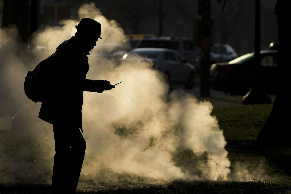 In this Nov. 30, 2012 photo, a pedestrian looks at his phone near steam vented from a grate near the Philadelphia Museum of Art on a cold morning in Philadelphia. Every time a person shops online or at a store, loyalty cards linked to phone numbers or email addresses can be linked to other databases that may have location data, home addresses and more. Voting records, job history, credit scores (remember the Equifax hack?) are constantly mixed, matched and traded by companies in ways regulators havent caught up with.