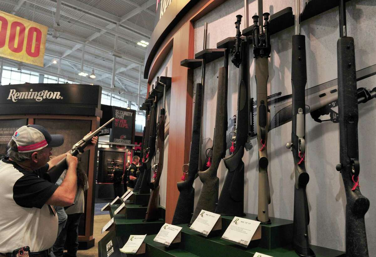 In this photo taken on April 10, 2015 a convention attendee looks at a Remington bolt action rifle at the 2015 NRA Annual Convention in Nashville, Tennessee. The US gunmaker Remington filed for bankruptcy protection on March 25, 2018, a day after marchers swarmed US cities nationwide to call for greater regulation of firearms.But the hard times now facing gun companies began in November 2016.That was when Donald Trump's surprise election victory in the US led to a sudden drop in US firearms demand, which had been until then as gun owners stockpiled in anticipation of a Hillary Clinton presidency.