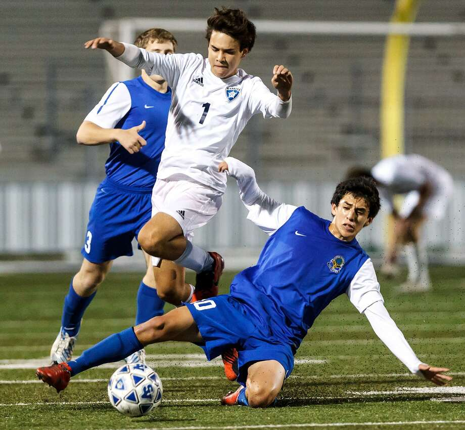 MacArthur's Nico Loera (right) slides in front of Smithson Valley's Diego Martinez to try to steal the ball as Elliot Clark looks on during the second half of their 5A first round playoff game at Smithson Valley on Thursday, March 28, 2013.  MacArthur beat the Rangers 1-0.  Photo by Marvin Pfeiffer / Prime Time Newspapers Photo: MARVIN PFEIFFER, STAFF / Marvin Pfeiffer / Prime Time New / Prime Time Newspapers 2013