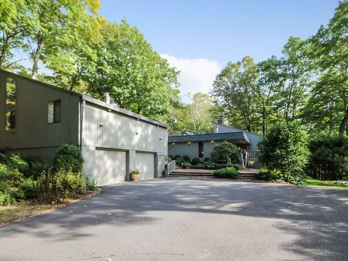 The gray contemporary house at 81 Grey Rocks Road sits on a 2.65-acre property near Weir Farm National Historic Site and Quarry Head Park.