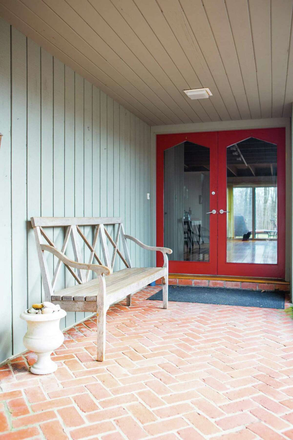 The entrance into the main house is from the covered red brick breezeway and through French doors.