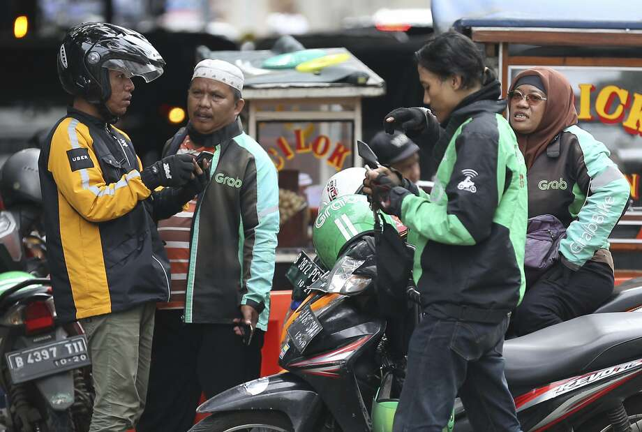 An Uber rider talks with Grab rider in Jakarta, Indonesia. San Francisco's Uber is selling its business in Southeast Asia to regional rival Grab in its latest withdrawal from a daunting overseas market. Photo: Achmad Ibrahim, Associated Press