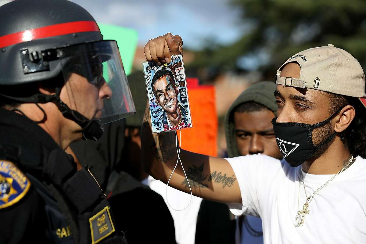 A Black Lives Matter protester holds a photo of Stephon Clark in front of a California Highway Patrol officer as they block an entrance to Interstate 5 during a demonstration on March 23, 2018 in Sacramento.