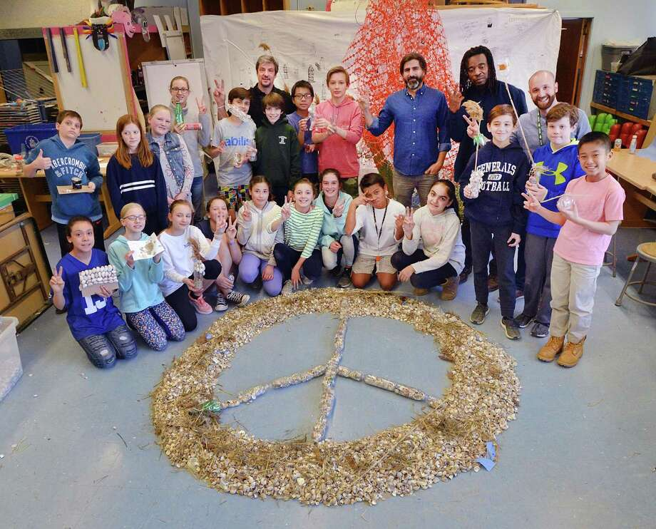 "Posing for a photo, Eastern Middle School sixth grade students with the help of visiting environmental artists, Willie Cole and Alejandro Duran, created a peace sign made of seashells, plastic pollution and discarded items collected from Tod's Point as part of their ""Message in a Bottle"" art project dealing with pollution, done during class at the school in Greenwich, Conn., Friday, March 23, 2018. Photo: Bob Luckey Jr. / Hearst Connecticut Media / Greenwich Time"