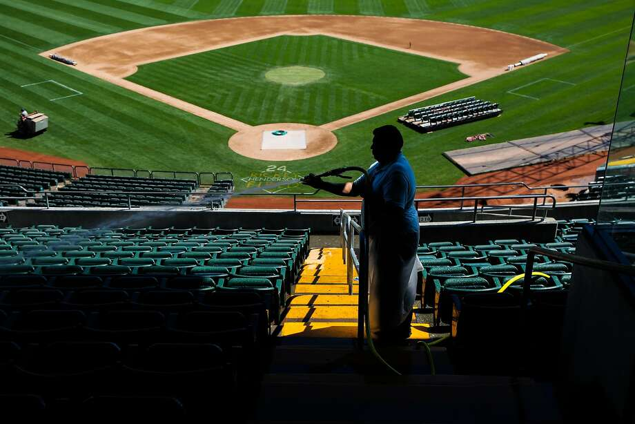 Worker Jose Brargas washes the seats while the field is being converted from baseball to football in August 2017. Photo: Gabrielle Lurie, The Chronicle
