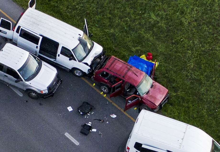 Officials investigate near a vehicle, center, where a suspect in the deadly bombings that terrorized Austin blew himself up as authorities closed in on him, in Round Rock, Texas, Wednesday, March 21, 2018. (Jay Janner/Austin American-Statesman via AP) Photo: Jay Janner, MBO / Associated Press / Austin American-Statesman