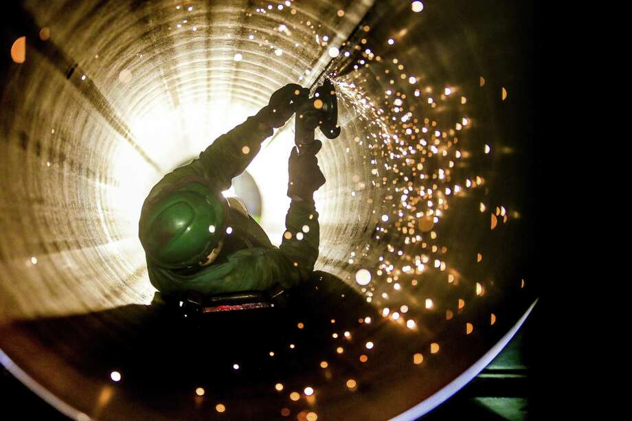 JSW Steel grinder Juan Silva smooths out the inside of a steel pipe Thursday, September 1, 2016 in Baytown. ( Michael Ciaglo / Houston Chronicle ) Photo: Michael Ciaglo, Staff / Houston Chronicle / © 2016  Houston Chronicle
