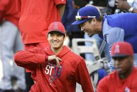 Angeles Angels' Shohei Ohtani, left, of Japan, talks with Los Angeles Dodgers' Kenta Maeda, right, also of Japan, as he stretches prior to a preseason baseball game Monday, March 26, 2018, in Los Angeles. (AP Photo/Mark J. Terrill)