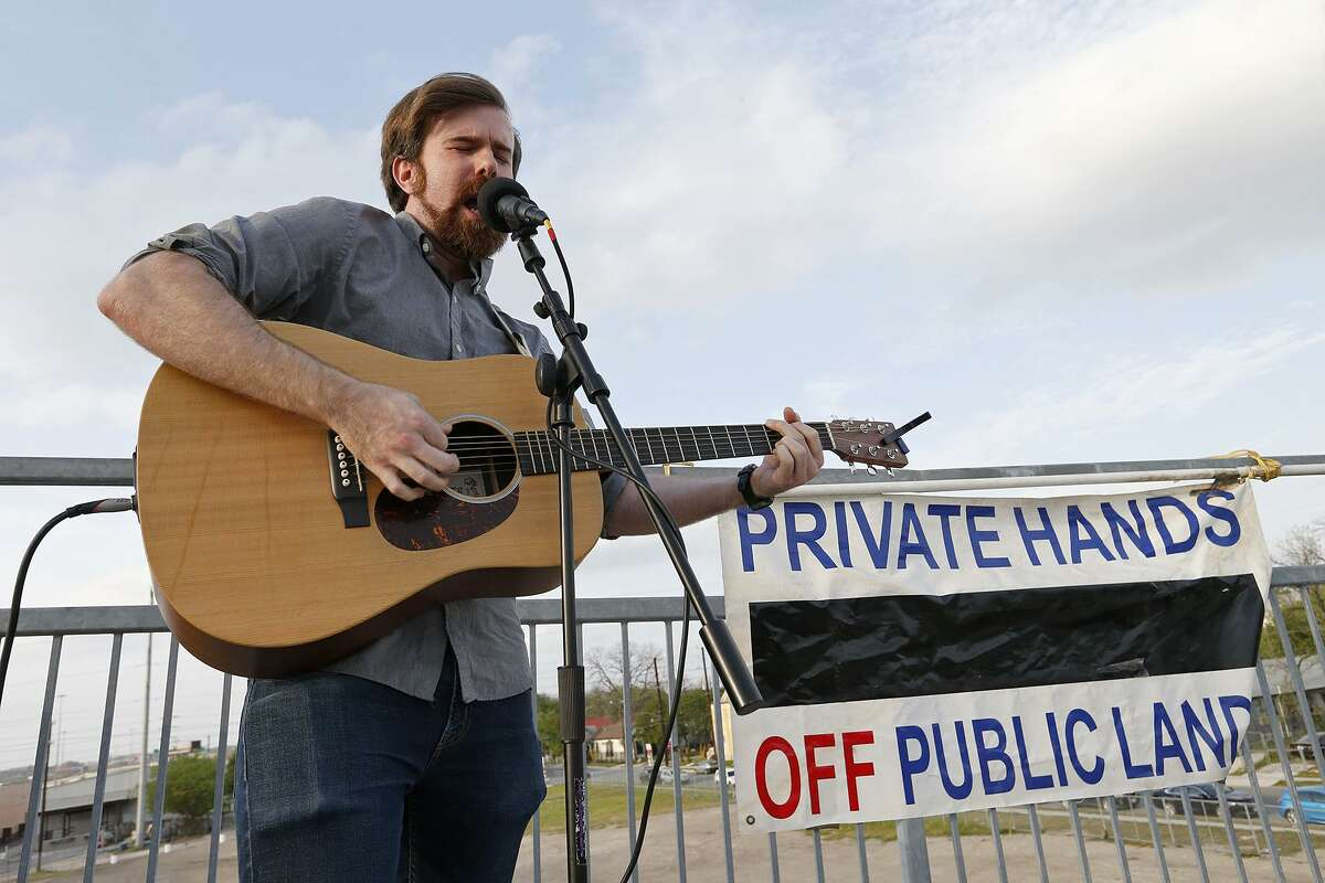 Will Parker, of the band Junkyard Fort, performs during a vigil, against the apartment complex proposed on contested land next to the Hays Street Bridge.