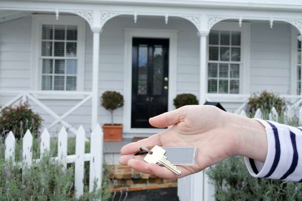 A womans hand holds a key against a front of a traditional villa house in Auckland, New Zealand. Buy, sale, real estate, insurance, mortgage, bank loans and housing market concept. (Photo by: Gonzales Photo/PYMCA/Avalon/UIG via Getty Images)