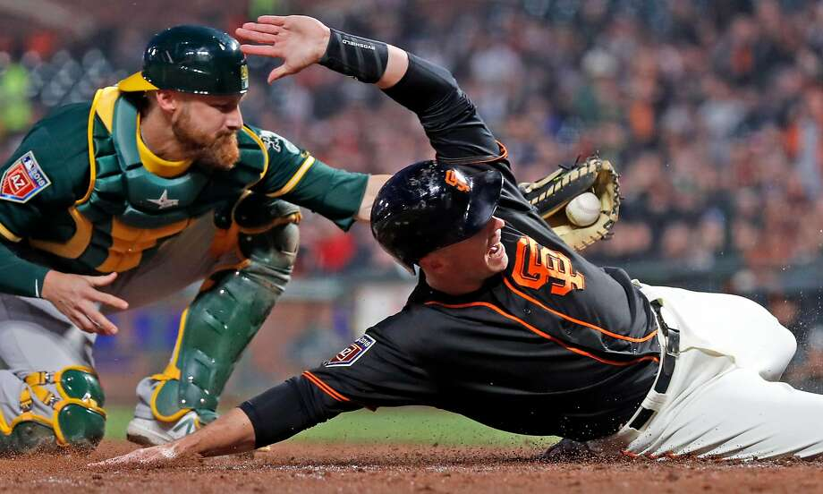 Catcher, meet catcher: The Giants' Buster Posey scores on a Hunter Pence single Monday, sliding by the A's Jonathan Lucroy. Photo: Scott Strazzante / The Chronicle