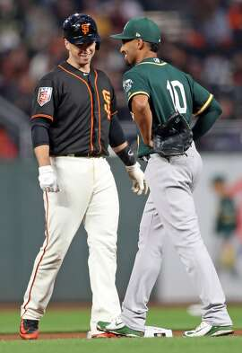 San Francisco Giants' Buster Posey and Oakland Athletics' Marcus Semien exchange pleasantries after Posey doubled in 2nd inning during Bay Bridge Series game at AT&T Park in San Francisco, Calif., on Monday, March 26, 2018.