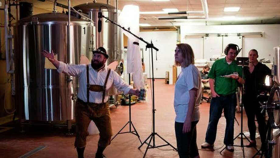 Actors Drew Korpal and Rachel Farley act in a video at Midland Brewing Co. Aberro Creative employees Chris Lones and Kimberly Cronk monitor the action. (Photo provided)