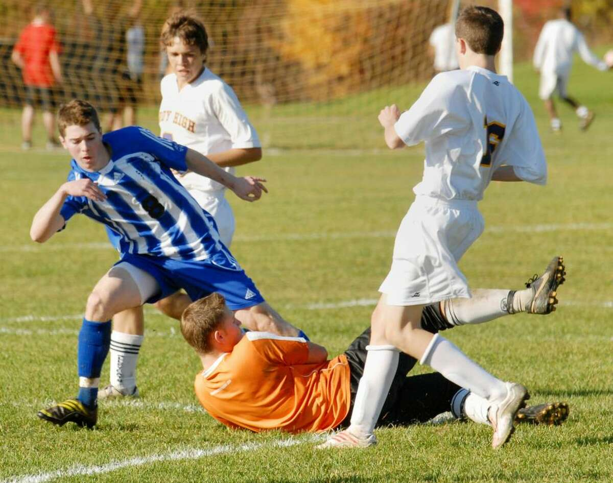 Shaker's Kevin Lennon, left, tries to force Troy goalie Zachary Scher to lose control of the ball. (Luanne M. Ferris / Times Union)