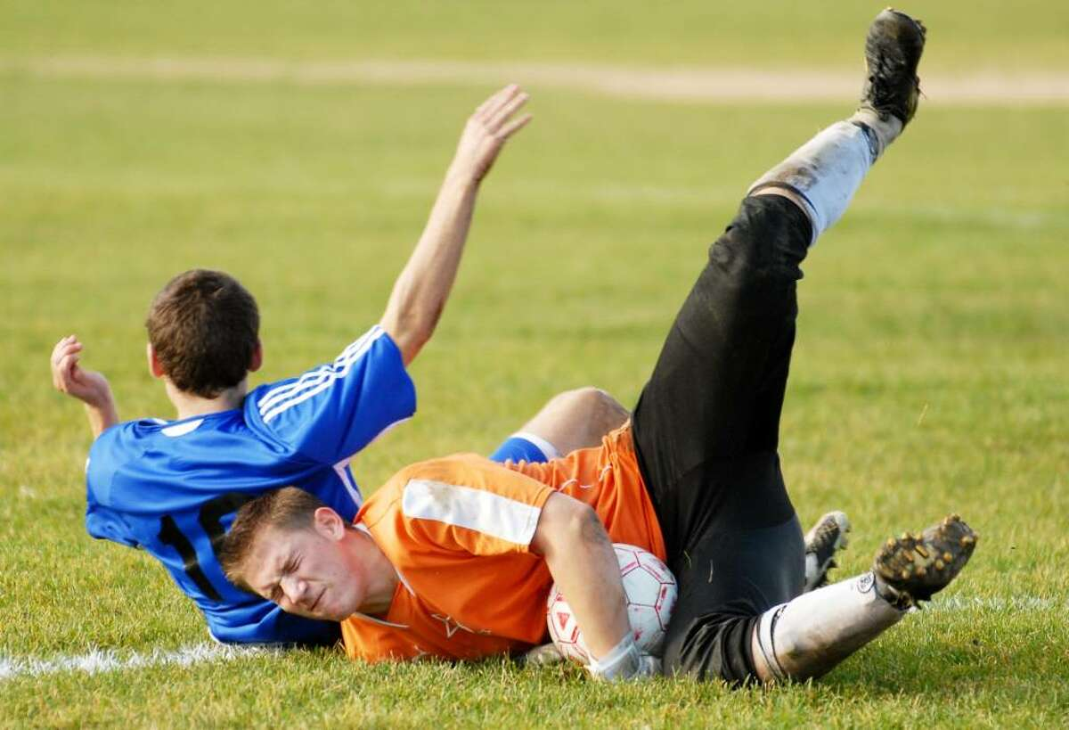 Shaker's Jackson McCarthy, left, collides with Troy goalie Zachary Scher. (Luanne M. Ferris / Times Union)