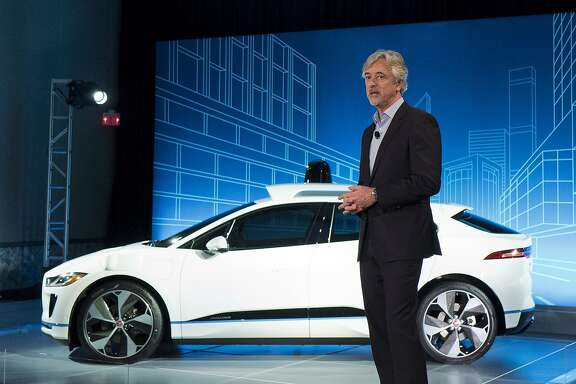 John Krafcik, the CEO of Waymo, stands with the Jaguar I-Pace vehicle, Tuesday, March 27, 2018, in New York. Self-driving car pioneer Waymo will buy up to 20,000 of the electric vehicles from Jaguar Land Rover to help realize its vision for a robotic ride-hailing service. The commitment announced Tuesday marks another step in Waymo's evolution from a secret project started in Google nine years ago to a spin-off that's gearing up for an audacious attempt to reshape the transportation business. (AP Photo/Mark Lennihan)