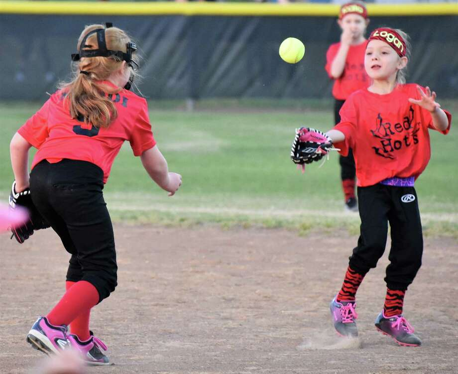 Red Hotz player Maddi Raybion throws to teammate Logan Henke to get an Explosion player out at first. Monday, March 19, marked opening day for Needville Little League, with this match-up between Red Hotz vs Xplosion. Photo: Beverlie Pollock